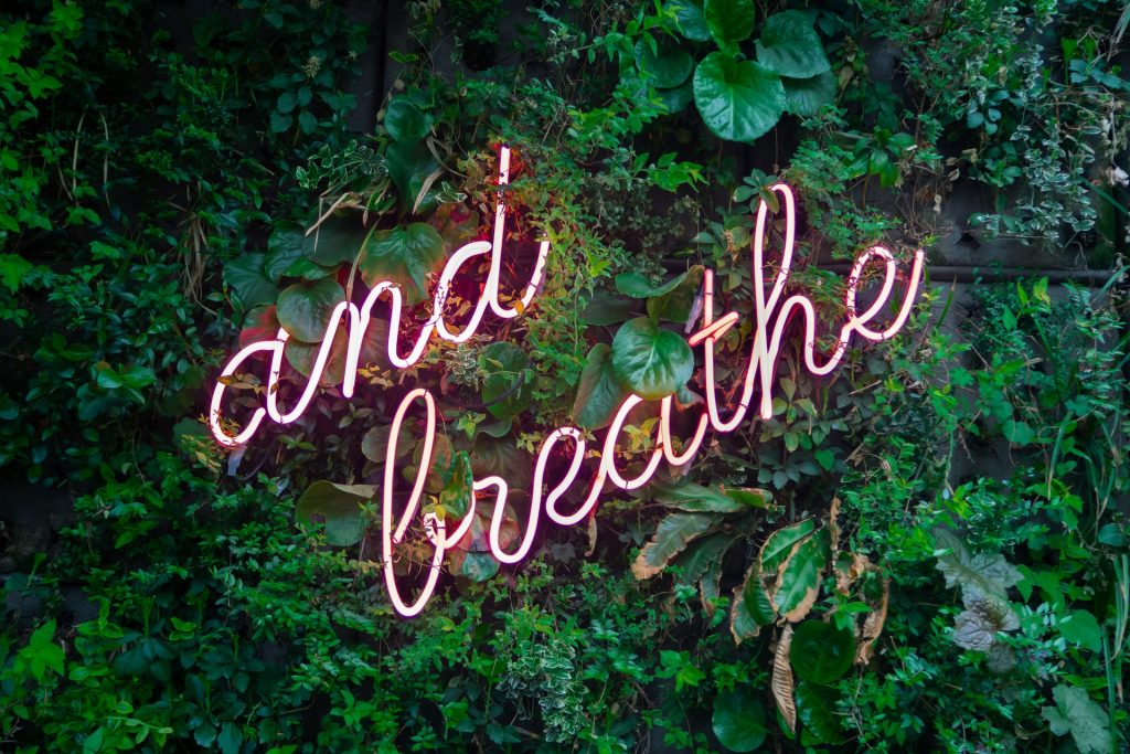 neon sign reminder to breathe and take breaks to improve your art