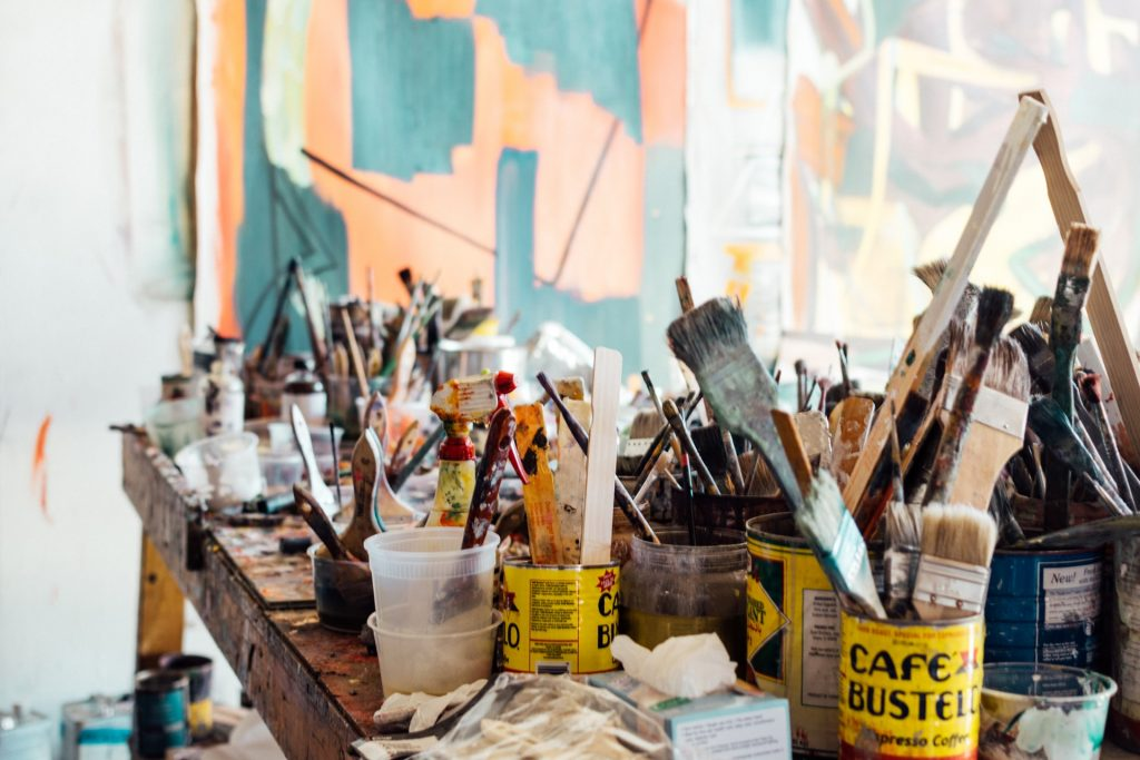 cans of paint brushes to create art, not imitate it